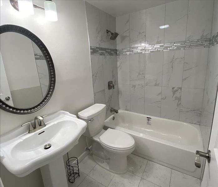 white bathroom with tub, sink and toilet