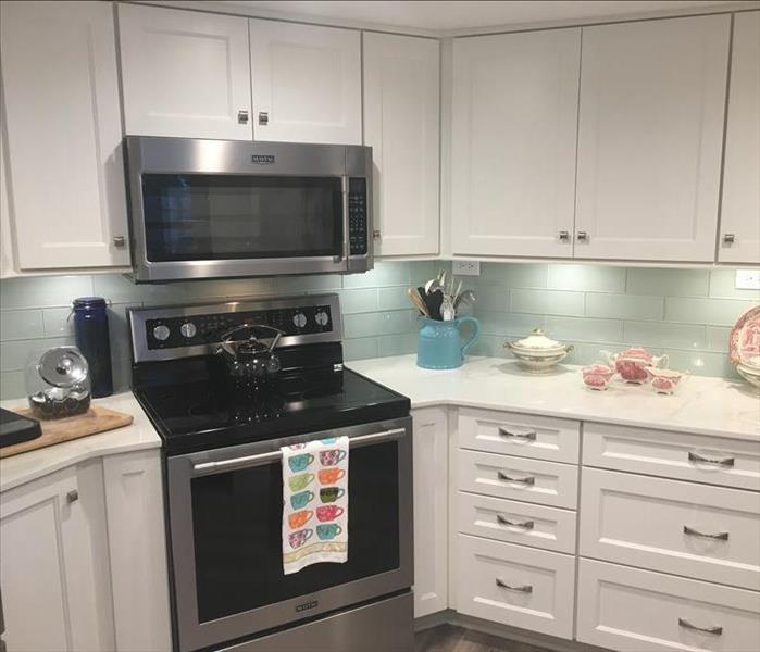 kitchen with white cabinets and teal backsplash with black oven