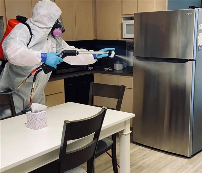 man wearing white tyvek suit spraying a fridge with disinfectant