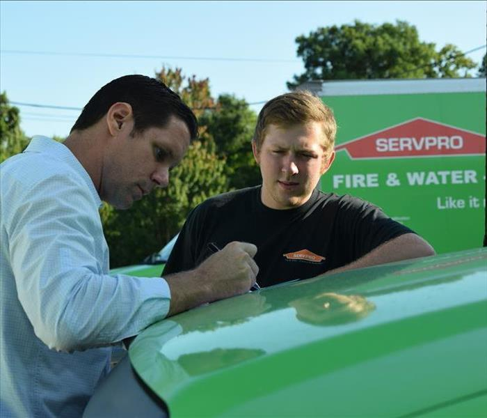 two men standing by a green truck