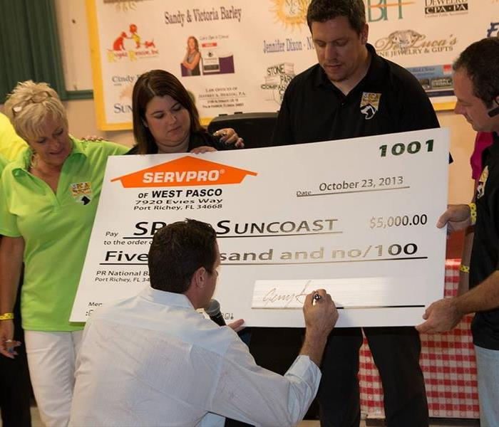 two women and a man holding a large check and a man in white shirt signing it
